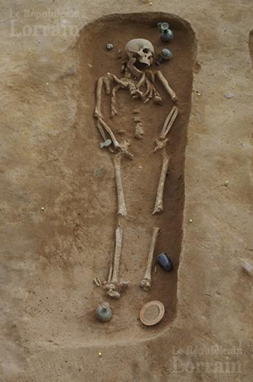 Cette photo montre la position du corps dans l une des tombes on peut voir les flacons en verre et les pots en ceramique qui l entourent photo pole archeologie preventive de metz m